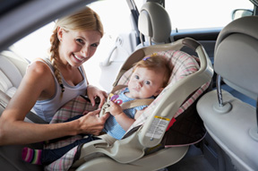 picture of a mom putting her kid in a car seat on the defective product service page of heintz & becker