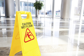 caution wet floor sign on a Premises Liability service page for a florida injury law firm
