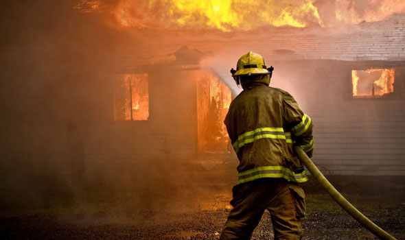 fire fighter hosing down a flaming house is the featured image on Heintz & Becker's burn injury page